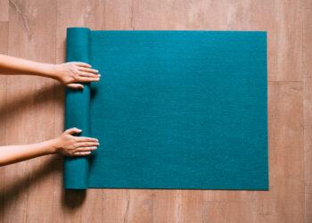Žena preklapa plavu prostirku za vježbanje